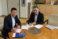 Thomas Jordans und Schulleiter Dr. Uwe Bettscheider unterschreiben den Kooperationsvertrag