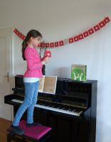 Livia steht auf einem Klavierhocker und angelt sich ein Gutschein-Briefchen