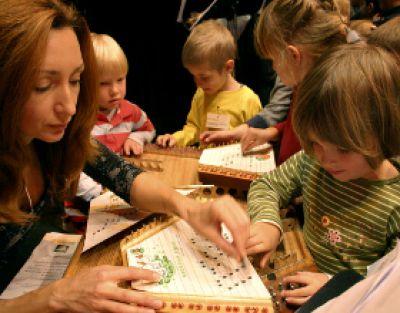 Die Kinder probieren das außergewöhnliche Instrument Cimbaly aus