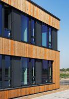 Die vertikale Schalung aus Lärchenholz mit orangenen Farbakzenten prägt die Fassade des Büroneubaus. Foto: Brüninghoff