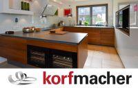 Traumküche mit grifflosen Fronten in Nussbaum massiv sowie aus weißem Glas (Hochschrank) und 12 mm dünner Keramik-Arbeitsplatte.