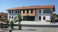 Monolithisches Rathaus in Schnaitsee: Mit einem Fries aus Lärchenholz wird das Satteldach von der Außenwand optisch entkoppelt.