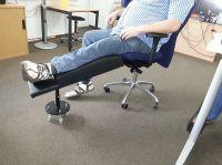 Bürodrehstuhl mit Beinauflage für ein steifes Bein