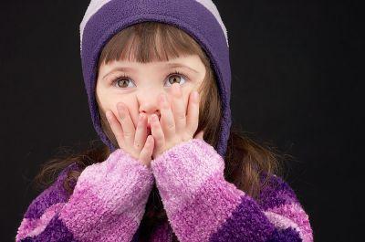 Mutistisches Mädchen hält sich den Mund zu