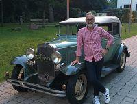 Auktionator Frank Ehlert mit einem Oldtimer der Auktion, dem Chevrolet Phaeton Landauer von 1931