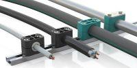 DIN-Schellen von Stauff nun neben Rohren und Schläuchen für weitere Leitungsarten optimal nutzbar: Elektrokabel und Wellschläuche