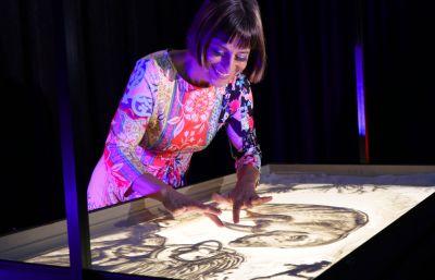 Künstlerin Sabrina beim Ausüben der Sandmalerei
