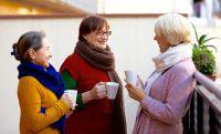 3 Frauen die auf dem Balkon stehen und Kaffe trinken und sind glücklich. Sie leben gemeinsam in einer PlusWG - SeniorenWG.