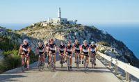Radrennfahrer vor dem Leuchtturm am Cap Formentor auf Mallorca