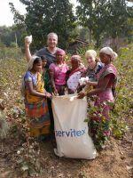 Erntehelfer mit Ellen Petow, Mitglied der Geschäftsführung der Servitex Wäscherei HESSE bei der Übergabe der Baumwollsäcke.