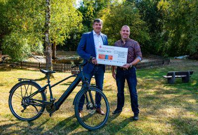 Michael Gruben (li.i.B.)  überreicht  Kai Leimig den Spendenscheck und ein E-Bike. Foto: Glatthaar Keller