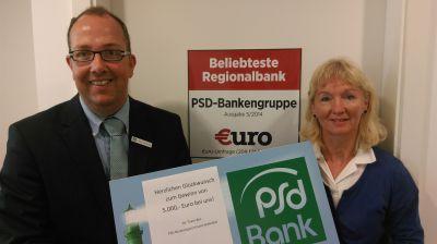 Carsten van de Loo, Leiter des PSD BeratungsZentrums Bielefeld gratuliert Marianne Schlesing zu ihrem Gewinn.
