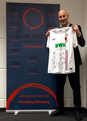 Geschäftsführer Nikolaus Seitz mit dem begehrten FCA Trikot